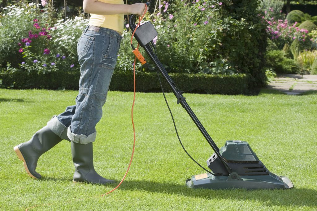 Woman using a small corded hover mower.