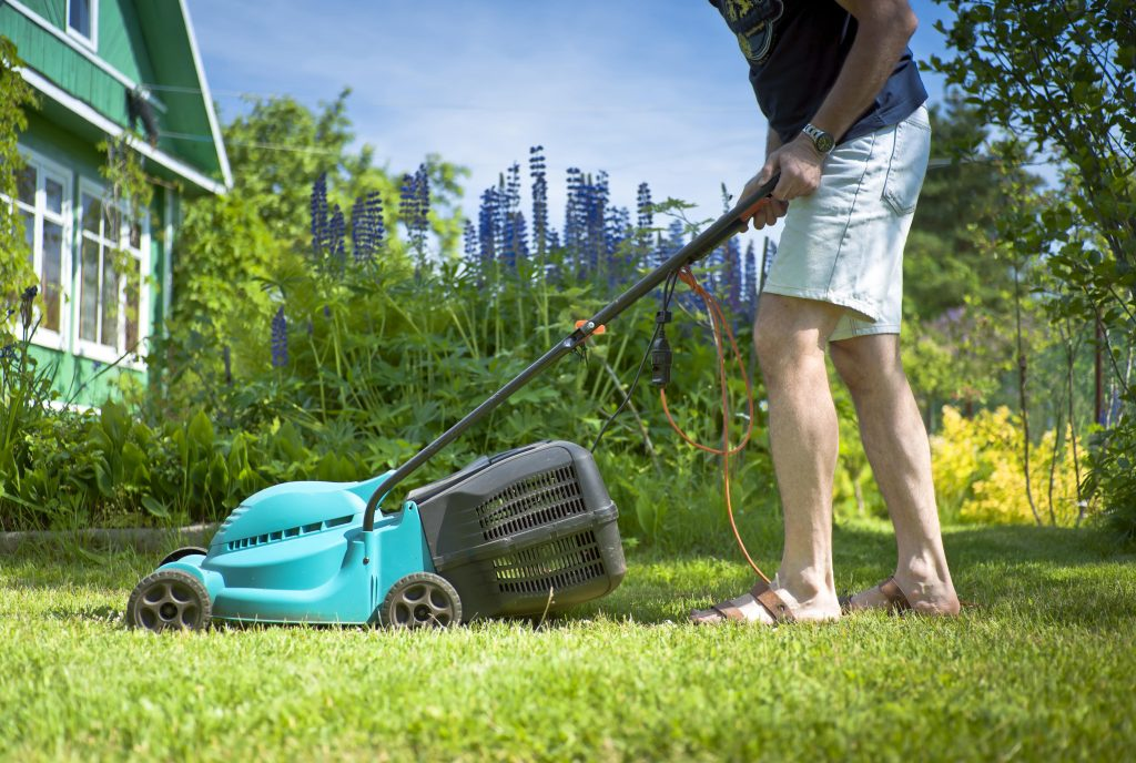 Man using a corded rotary lawn mower.