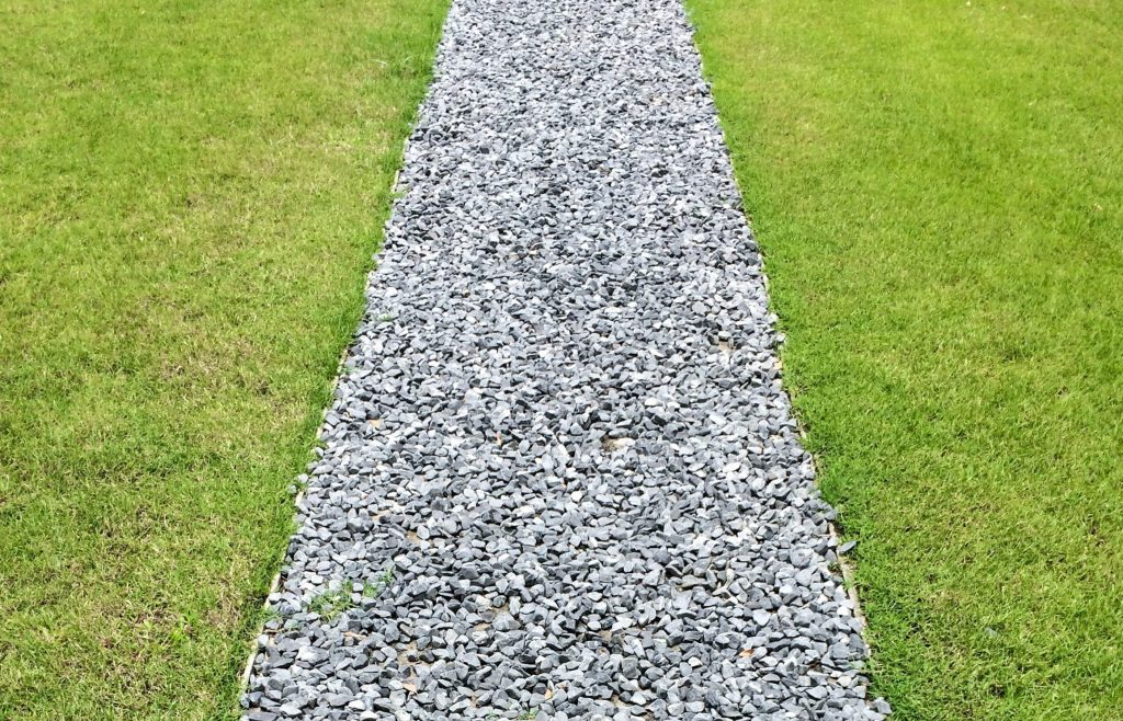 Crushed rock gravel path on a lawn.