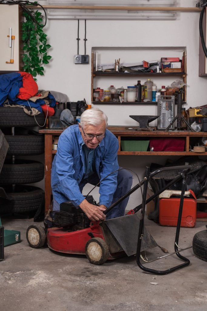 Lawn mower outside a garage being prepared for storage.