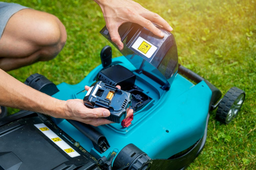 Man changing the battery on a cordless lawn mower.