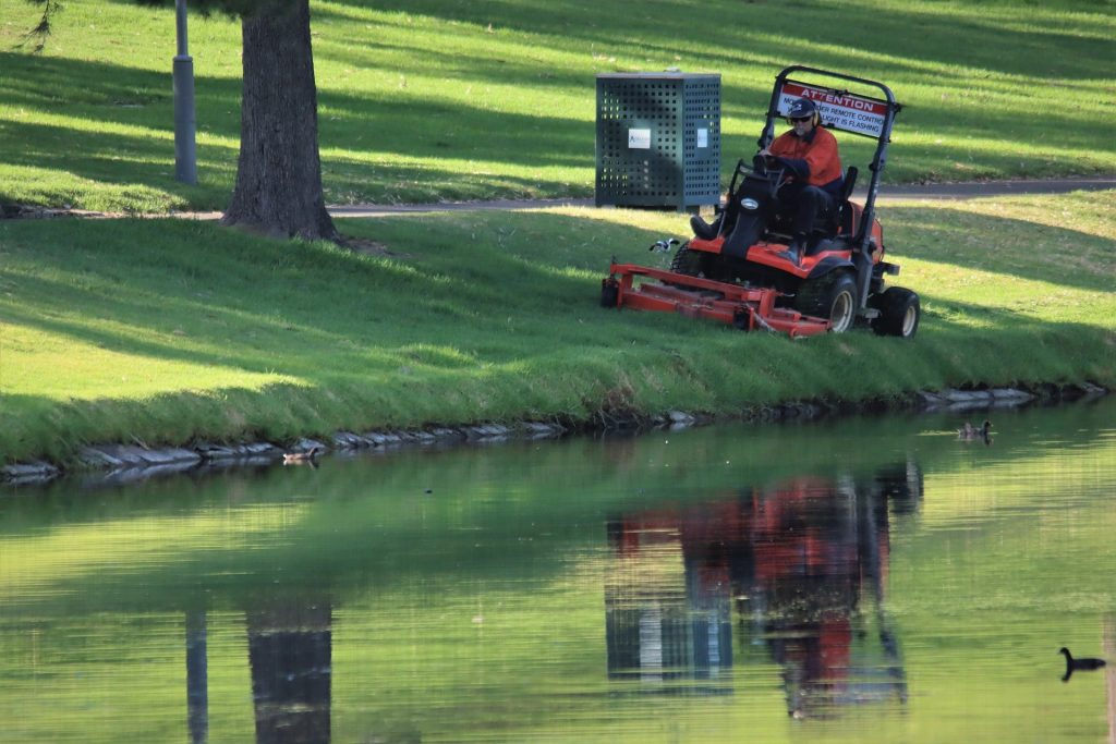 Man cutting lawn with a ride-on mower.