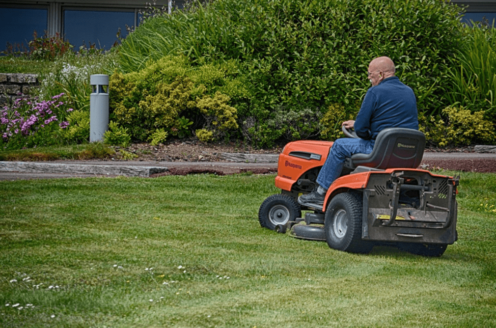Man mowing the lawn with a lawn tractor.