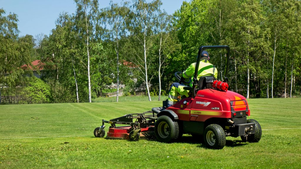 Man mowing a sport field with a ride-on lawn mower.