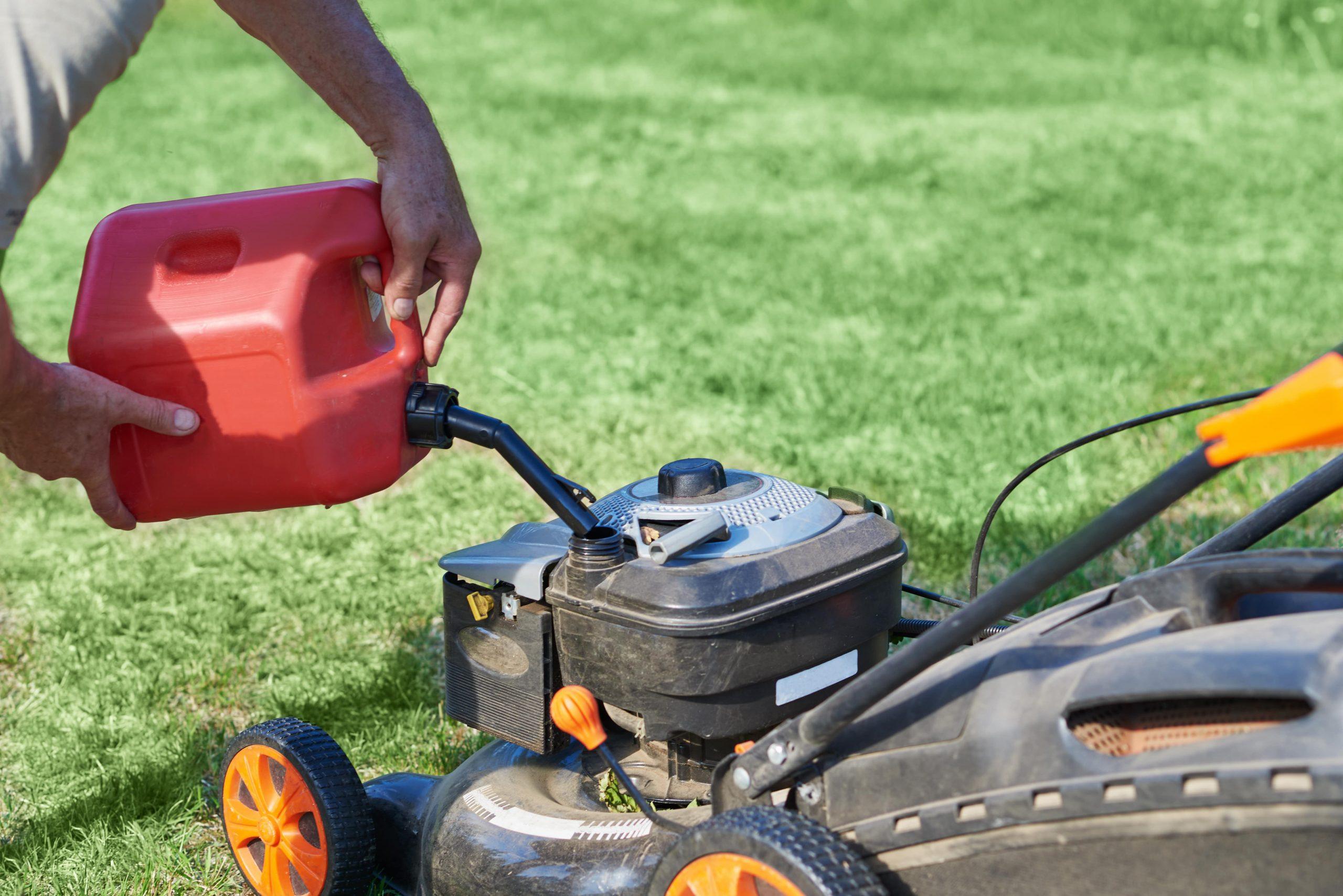 Man refueling lawn mower.