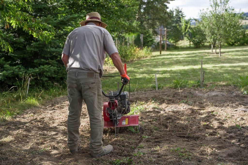Man using a tiller on an allotment.