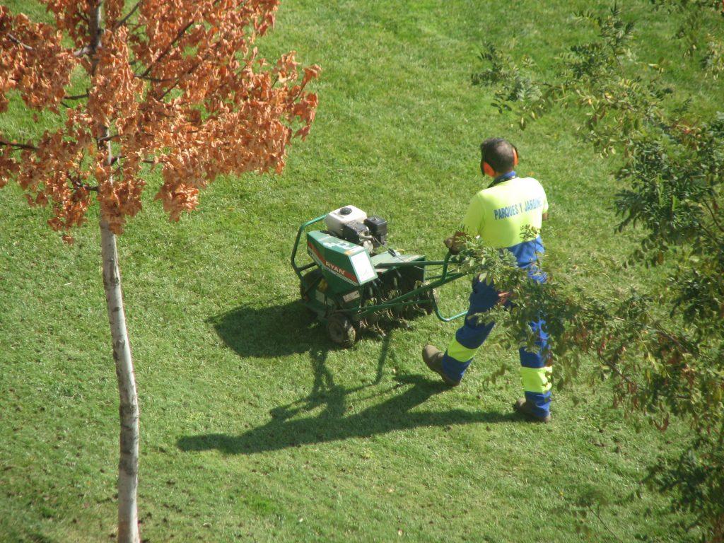 Man using a walk behind powered aerator.