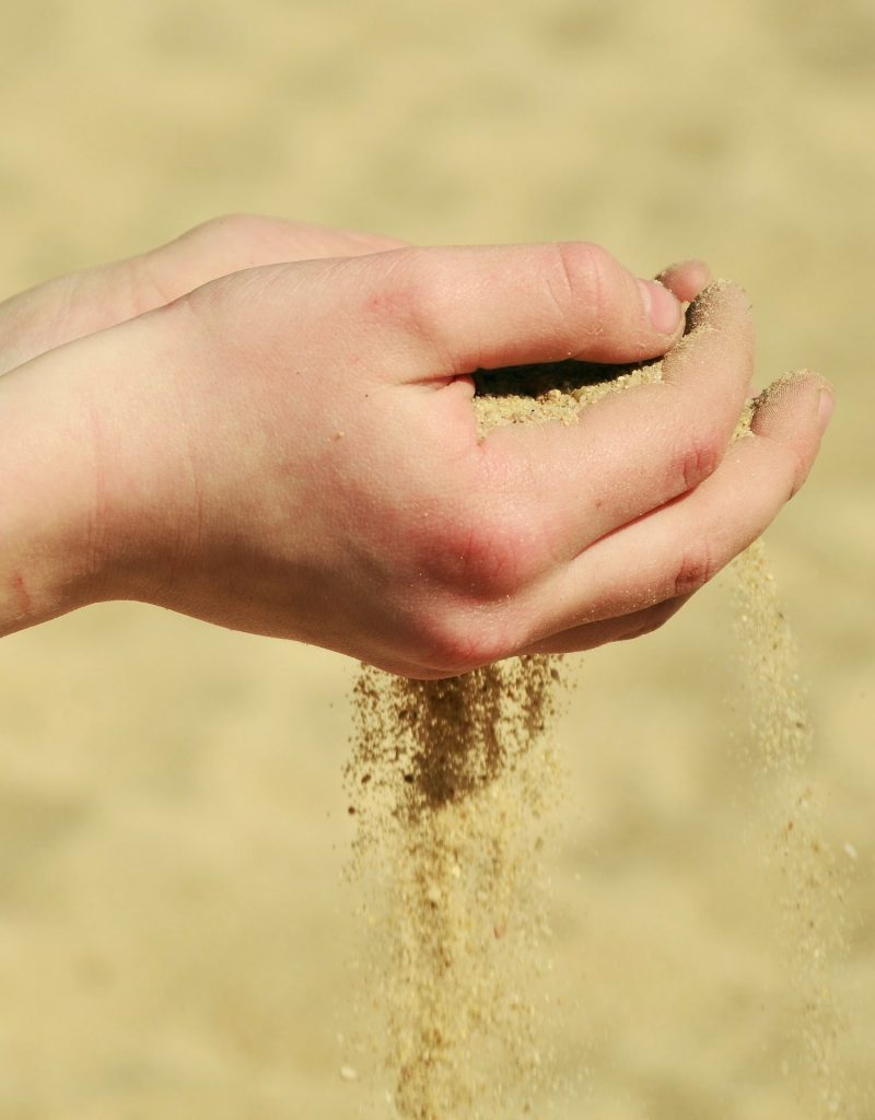 Person holding sand in their hands.