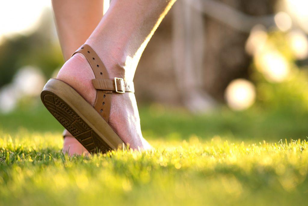Woman walking on a lawn.