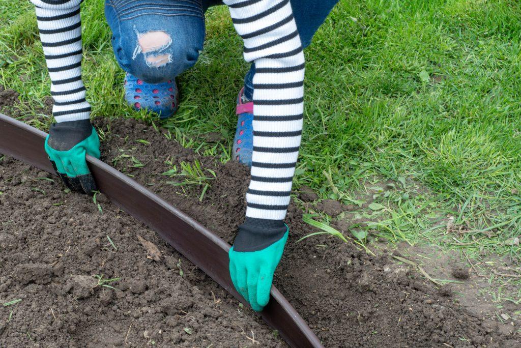 Woman installing a grass edge barrier.