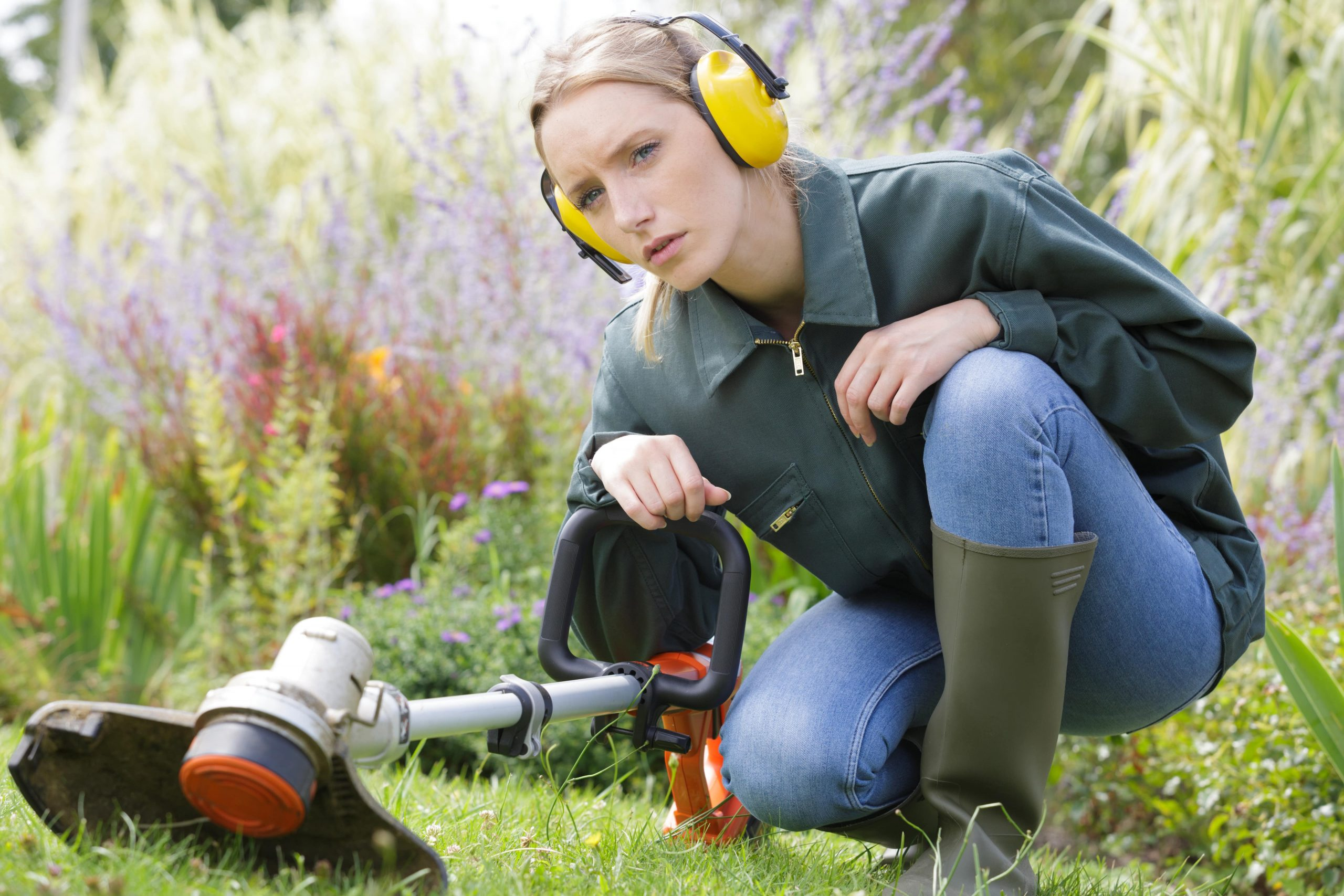 Woman using a cordless strimmer.