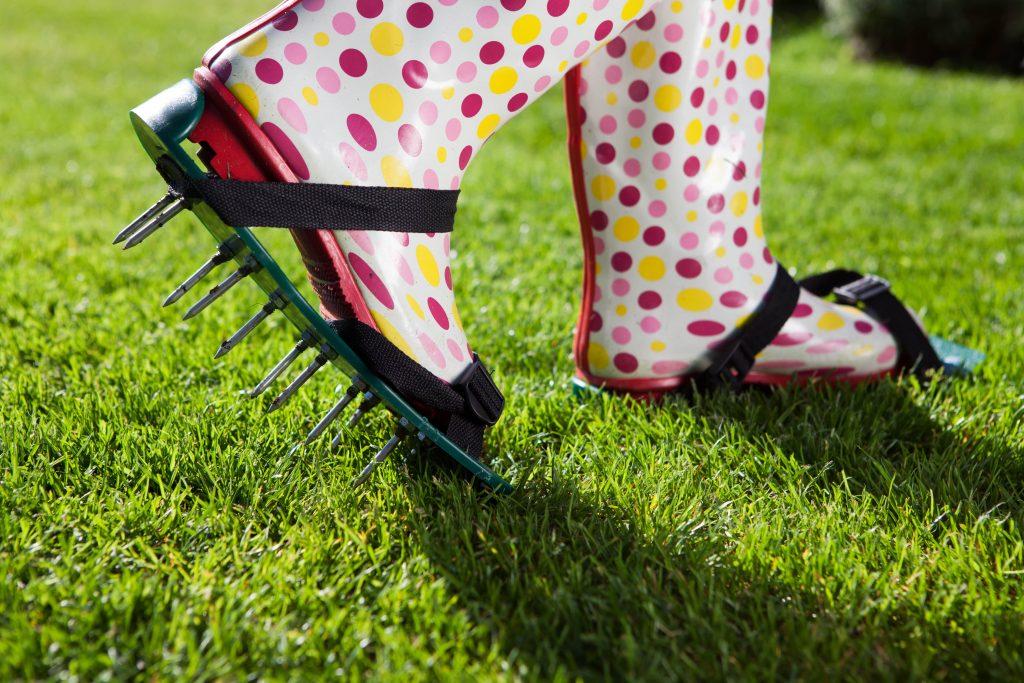 Woman walking in lawn aerator shoes.
